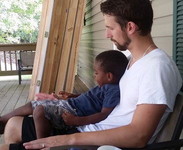 dad sits with child on porch | coyotehill.org