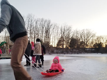 girl being pulled on sled on ice