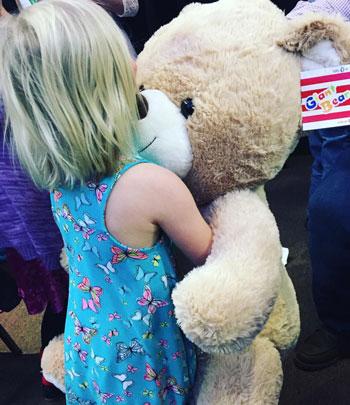 Child hugs teddy bear | coyotehill.org