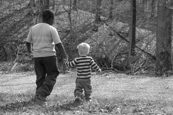 Bi-racial foster siblings walk while holding hands | coyotehill.org